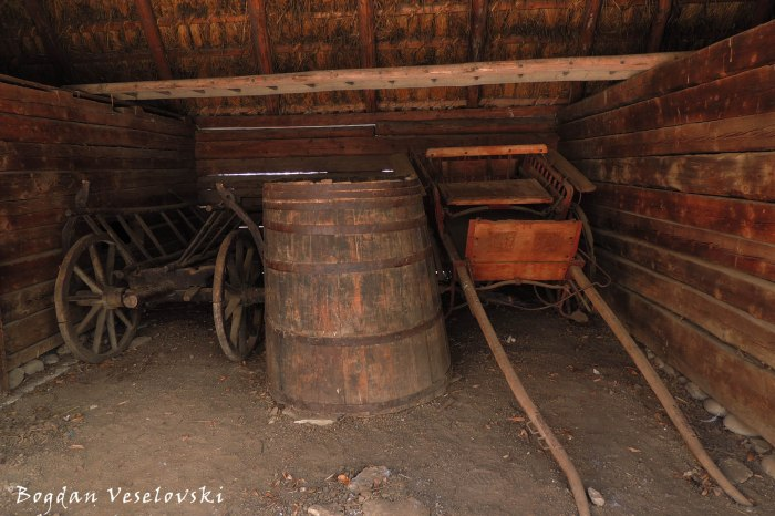 Carts and barrel in a barn